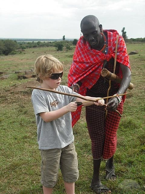 tips and tricks being passed down from a masai moran to a tourist kid